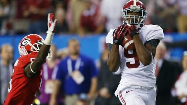 Wide receiver Amari Cooper of the Alabama Crimson Tide catches a fourth quarter touchdown pass in front of defensive back Damian Swann of the Georgia Bulldogs during the SEC title game in Atlanta.
