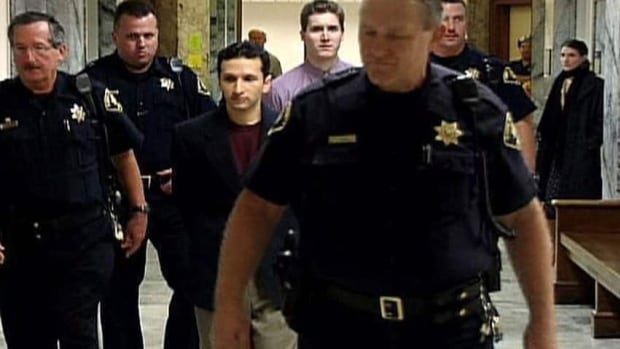 Glen Sebastian Burns (back, centre) and Atif Ahmad Rafay (third from left) are escorted by police in an image grab from a documentary, Mr. Big, made by Burns's sister, Tiffany Burns. (The Canadian Press)