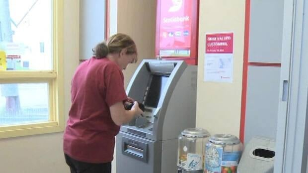 A woman uses the Scotiabank bank machine in Fortune. The company plans to remove the machine in the fall.