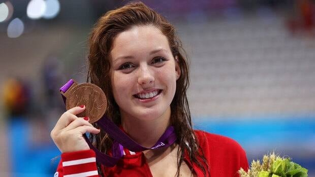 Summer Mortimer poses on the podium after winning bronze in the women's 100-metre freestyle on Thursday.