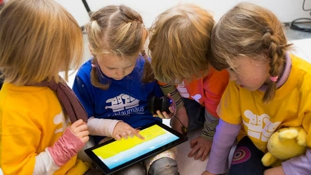 Children play with Microsoft's 'Schlaumaeuse' education software that runs on a Windows 8 operated tablet computer during the program's presentation in Berlin Nov. 8, 2012.