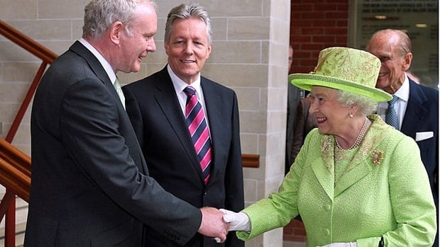 Queen Elizabeth shakes hands with Northern Ireland Deputy First Minister and former IRA commander Martin McGuinness, watched by First Minister Peter Robinson, centre, at the Lyric Theatre in Belfast on June 27, 2012.