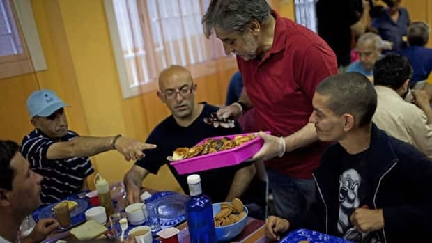 A volunteer serves a charity breakfast in Barcelona to help the unemployed and people without financial resources on Tuesday, the same day as the finance ministers of the G7 industrialized economies discussed Europe's debt crisis.