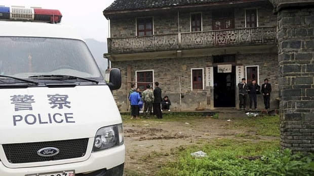 A police vehicle parks at the crime scene of the last Chinese school stabbing in 2010. A man stabbed 22 children on Friday.