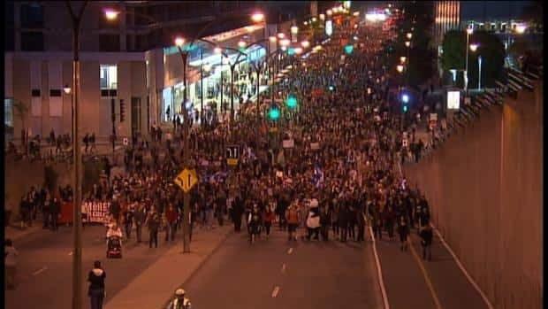 Thousands of people marched through Montreal later Friday night in defiance of a new protest law adopted at the Quebec legislature.