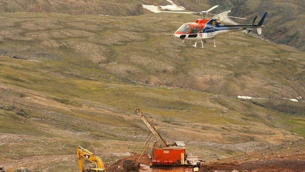 A helicopter passes over excavation equipment at the Mary River exploration camp, the site of a proposed iron mine on northern Baffin Island, in 2006 photo.