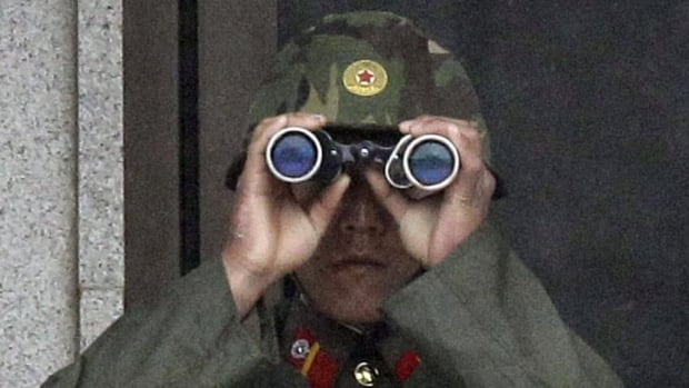 """A North Korean soldier looks at the southern side through binoculars at the Demilitarized Zone in April. On Friday, North Korea said it had detained a U.S. citizen whose crimes were """"proven by evidence"""""""