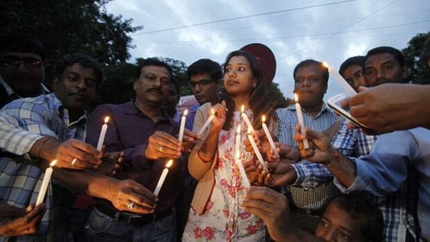 Indian journalists light candles and participate in a protest against the gang rape of a photojournalist in Bangalore, India, Saturday. The Thursday attack has provoked angry demonstrations across the country.