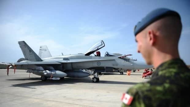 A Canadian soldier looks at a CF-18 as it sits loaded for flight at Camp Fortin on the Trapani-Birgi Air Force Base in Trapani, Italy, on Thursday, September 1, 2011.