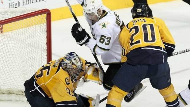 Dallas Stars center Mike Ribeiro, centre, is tripped up by Nashville Predators defenceman Ryan Suter, right, as goalie Pekka Rinne, left, blocks a shot by Ribeiro during their game Thursday night. The Predators won 2-0.