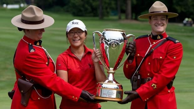Fifteen-year-old Lydia Ko, of New Zealand poses with the trophy with two members of the Royal Canadian Mounted Police after winning the CN Canadian Women's Open LPGA golf tournament at the Vancouver Golf Club in Coquitlam, B.C., on Sunday.
