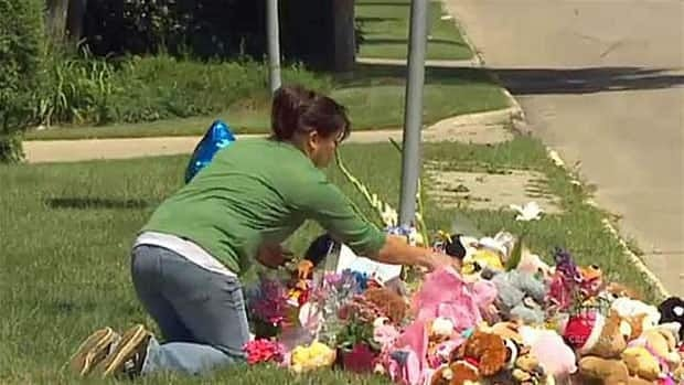A neighbour attends a makeshift memorial for Lisa Gibson and the family's two children near their Winnipeg home.
