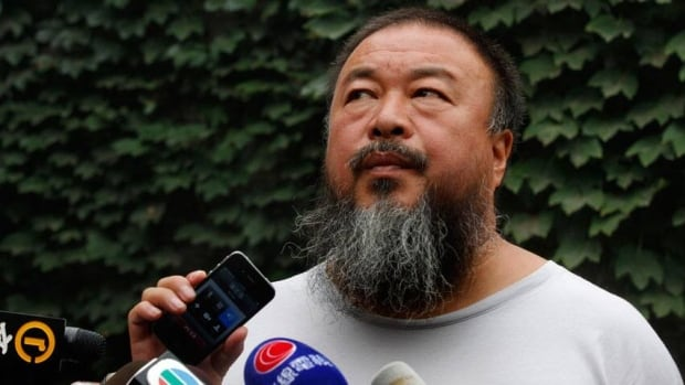 Ai Weiwei listens on Friday as his lawyer announces, via speakerphone, the verdict of the dissident artist's lawsuit challenging Beijing tax authorities.
