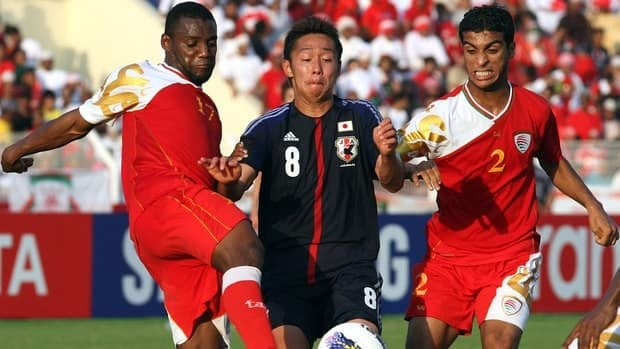 Oman's Mohammed al-Musalami, right, and Hassan Mudhafar, left, challenge Japan's Hiroshi Kiyotake during their 2014 World Cup Asian zone group B qualifying match in Muscat on Wednesday.