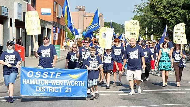 Teachers in Hamilton, shown here at a recent Labour Day parade, are protesting new legislation that imposes a wage freeze and bans their ability to strike for two years. Many Hamilton high school teachers will wear black on Wednesday.