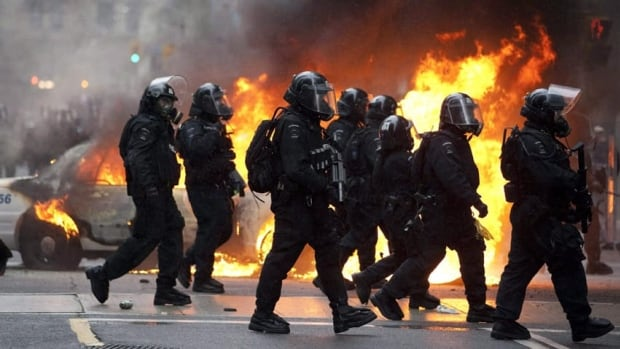 Riot police walk by a burning police car in downtown Toronto during anti G20 protests on Saturday, June 26, 2010.