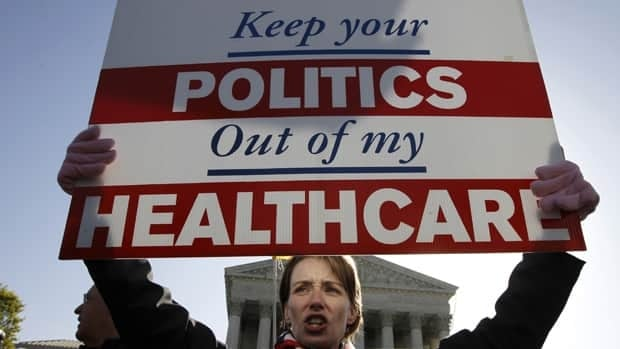 A demonstrator opposing health care reform rallies in front of the U.S. Supreme Court in Washington on Tuesday as the court continues arguments on the health care law.
