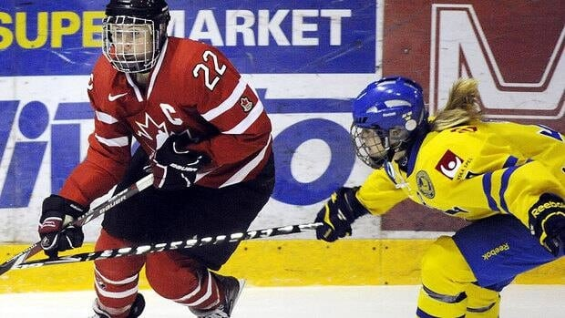 Canadian forward Hayley Wickenheiser, left, and Sweden's Frida Nevalainen battle during Friday's game in Finland. Canada earned a berth in the Four Nations Cup final with a 9-0 win.