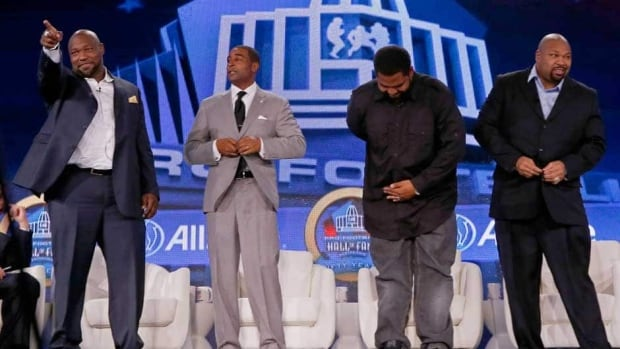 Former Tampa Bay Buccaneers lineman Warren Sapp, from left to right, former Minnesota Vikings wide receiver Cris Carter, former Baltimore Ravens player Jonathan Ogden, and former Dallas Cowboys player Larry Allen stand together after being named to the Pro Football Hall of Fame in February.