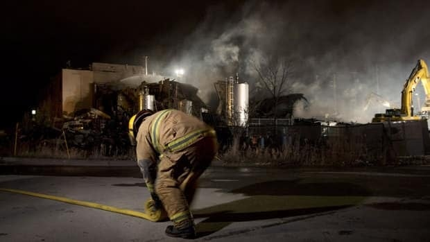 An emergency worker rolls up a hose outside Neptune Technologies and Bio Resources in Sherbrooke, Que., Thursday, Nov. 8, 2012 where a large explosion at the plant sent a number of people to hospital with serious injuries.