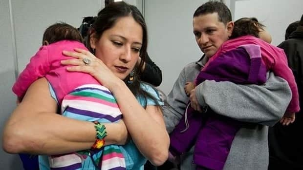 Mexican journalist Karla Ramirez, left, and her husband, Cesar Casso, carry their Canadian-born daughters after a news conference in Vancouver on Thursday.