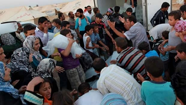 Syrian refugees crowd around to receive ice at the Al Zaatri refugee camp in the Jordanian city of Mafraq, near the border with Syria. Jordan opened the camp with 2,000 tents on Sunday, to accommodate an expected new influx of refugees near the border.
