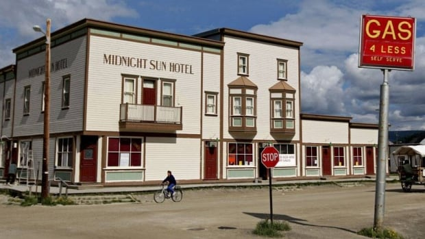 A cyclist, left, and horse-drawn tour travel past the Midnight Sun Hotel in Dawson City.