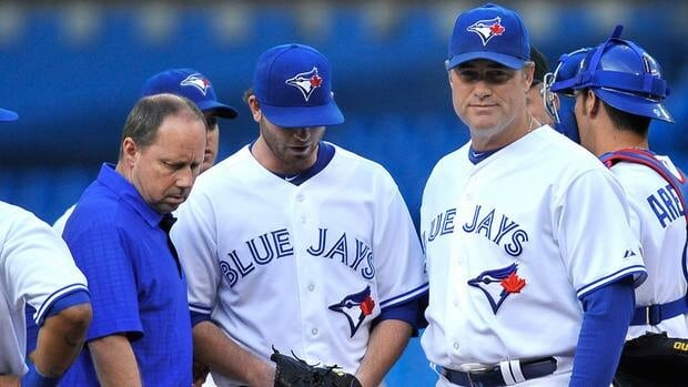 Assistant trainer Hap Hudson of the Toronto Blue Jays walks off the field with starting pitcher Drew Hutchison, centre, as manager John Farrell looks on during Friday's game against the Philadelphia Phillies.