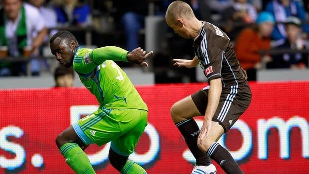 Whitecaps forward Kenny Miller, right, attempts to pull the ball around Seattle's Jhon Kennedy Hurtado, left, on Saturday at BC Place in Vancouver.