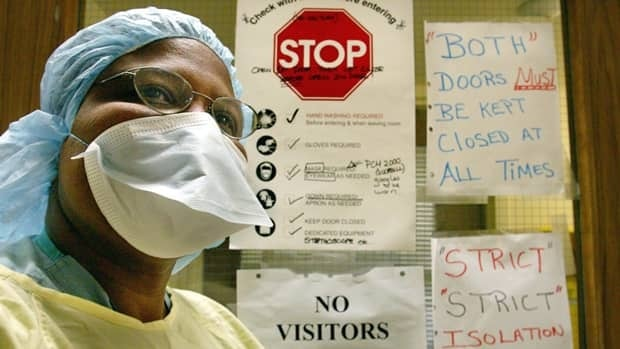 A nurse wears protective clothing to treat SARS patients at a Toronto hospital in 2003. The World Heath Organization has confirmed four more cases of a new virus, a cousin of the coronavirus that causes SARS.
