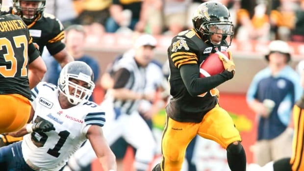 Tiger-Cats' Chris Williams avoids a tackle by Argonauts' Tristan Black on his way to a touchdown in Saturday night's game.