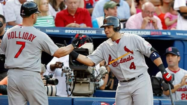 St. Louis Cardinals slugger Matt Holiday (7) celebrates his sixth-inning home run with teammate Yadier Molina, right, against the Atlanta Braves during the National League wild card playoff game on Friday.