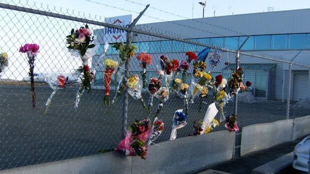 Flowers were spontaneously left at the fence near where passengers on Cougar Flight 491 had left St. John's. Families would like action on a proposed permanent memorial.