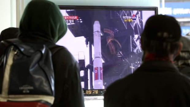 South Koreans watch a TV news program about North Korea's rocket launch plans at Seoul Railway Station on Sunday. North Korea has delayed the planned launch of the rocket.