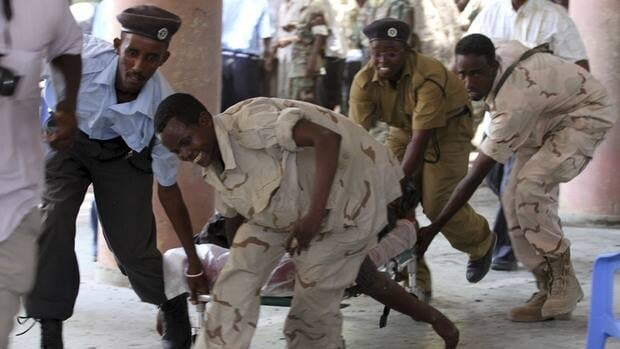Soldiers prepare to collect the body of the chairman of Somali football federation Said Mugabe after an explosion at the national theatre in Mogadishu on Wednesday.
