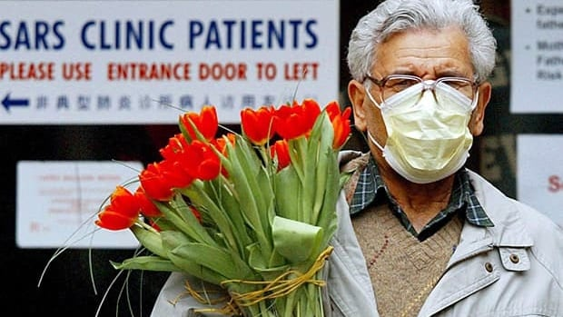 A man wears a protective mask as  at Women's College Hospital in Toronto March 28, 2003. Global health officials are closely following a new respiratory virus related to SARS that is believed to have killed at least one person in Saudi Arabia and left another person in critical condition in Britain.