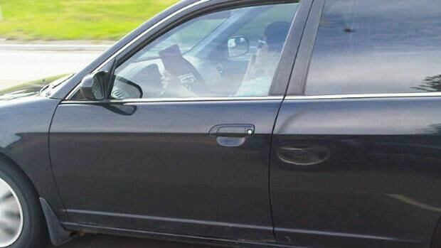 A woman holds what appears to be a book while driving in Calgary on Wednesday morning.