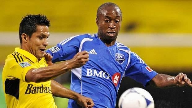 Crew's Jairo Arrieta, left, takes control of the ball in front of Impact's Collen Warner  in the first half.