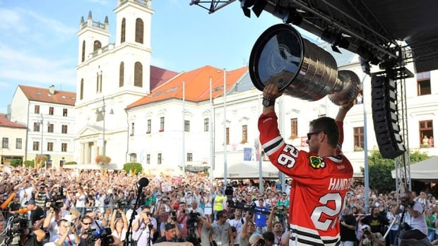 Michal Handzus of the Chicago Blackhawks holds the Stanley Cup as he arrives at main square in Banska Bystrica, Slovakia on August 8 during a tour of his hometown. The Hawks players have taken turns spending a day with the Cup this summer.