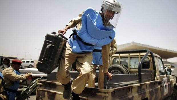 An explosives expert jumps from a military truck as he arrives at the site of a suicide bomb attack at a parade square in Sanaa on Monday.
