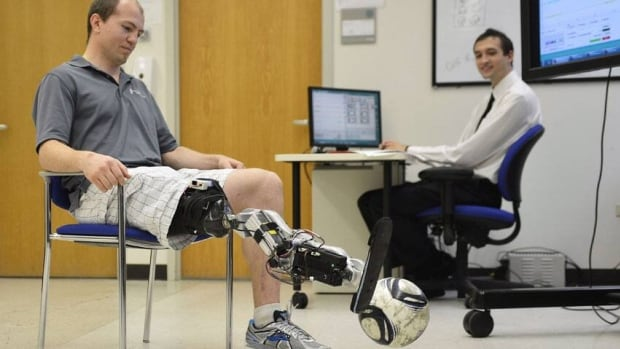 Amputee Zac Vawter kicks a soccer ball with an experimental, thought-controlled bionic leg as biomedical student Aaron Young makes adjustments at the Rehabilitation Institute of Chicago.
