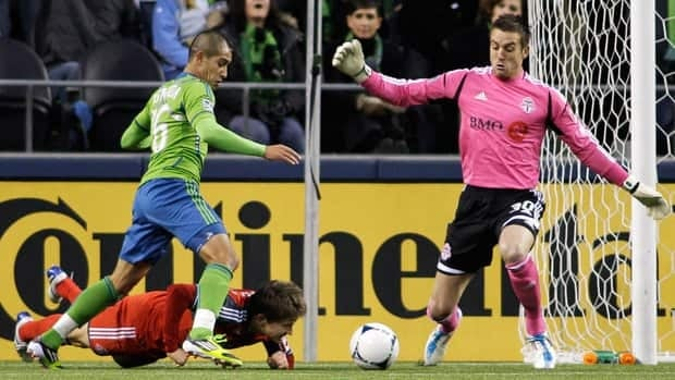 As Toronto FC's Terry Dunfield goes down at left, Toronto goalkeeper Milos Kocic, tries to stop Seattle Sounders' David Estrada (16), but Estrada got past Kocic and scored a goal in the first half on Saturday in Seattle.