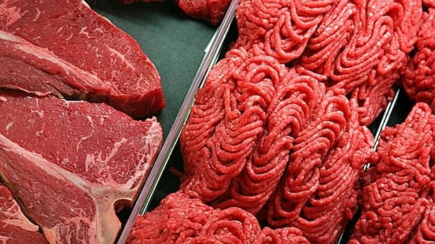 Ground beef and steaks on display at a deli counter.