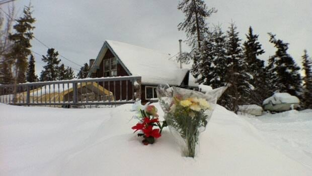 Flowers laid at the house in the Porter Creek neighbourhood yesterday where five people died, including two school-aged children.