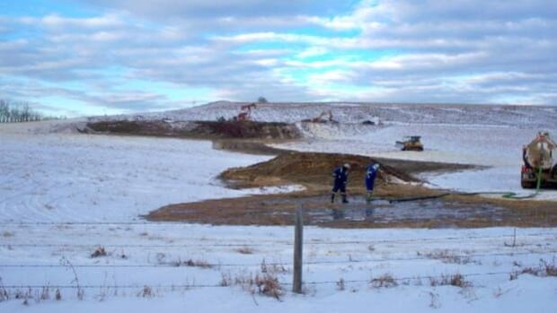 Workers clean up the site of the oil well blowout that occured near Innisfail on Jan. 13.