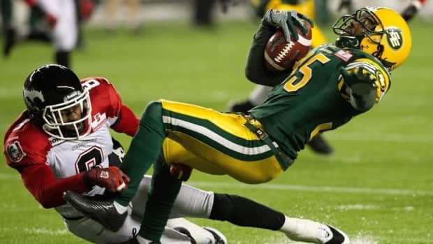 Edmonton Eskimos' Weldon Brown is tackled by the Calgary Stampeders' Fred Bennett, during the first half at Commonwealth Stadium on Friday, Nov. 2, 2012.
