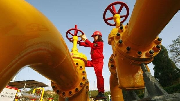 A worker checks the pressure at a natural gas pipeline in China. Beijing moved to pump more stimulus into its economy on Thursday by lowering lending rates.