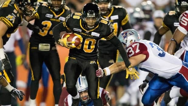 Hamilton Tiger-Cats' Chris Williams runs the ball past the Montreal Alouettes players on Friday. Williams scored a touchdown to help his team to a 41-28 victory.