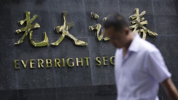 A man walks past the sign of Everbright Securities Ltd. in Shanghai. Everbright, one of China's biggest securities firms, has been fined $90 million after computerized trading mistakes caused wild swings in Chinese stock prices on Aug. 16.