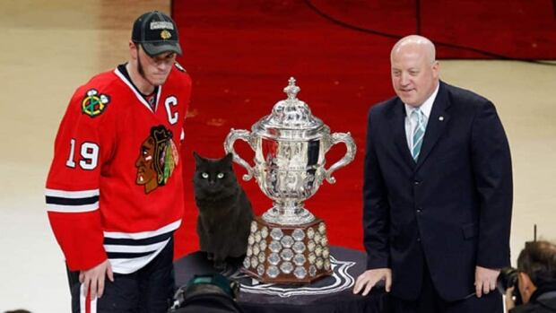 Jonathan Toews, a bad luck charm and Bill Daly stand around the Clarence S. Campbell Bowl in 2010.